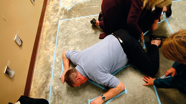 Patrons work to create images with blue tape.