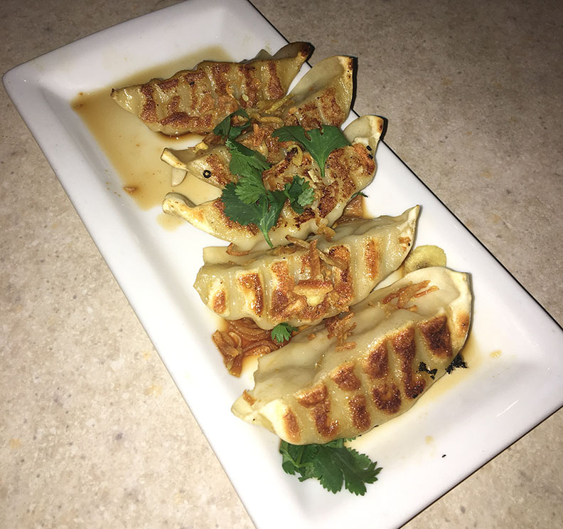 Gyoza Umani , pork dumplings topped with fresh cilantro, French fried onions and an Umani sauce.